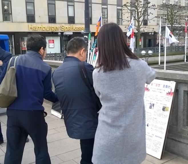 Tiga pengunjung dari Tiongkok mengambil foto tentang informasi Falun Gong